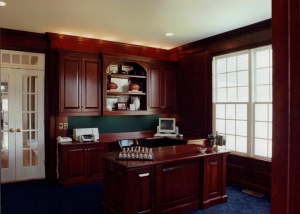 "This ""Home Office"" was designed and fabricated out of cherry hardwood and veneer. All four walls of the room feature a combination of built-in cabinets, bookshelves, and wainscoting. A freestanding desk was also designed for the office."